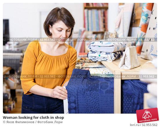 Woman looking for cloth in shop. Стоковое фото, фотограф Яков Филимонов / Фотобанк Лори