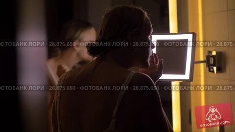 Купить «Woman looking in bathroom mirror after applying facial cream», видеоролик № 28875650, снято 19 февраля 2019 г. (c) Данил Руденко / Фотобанк Лори