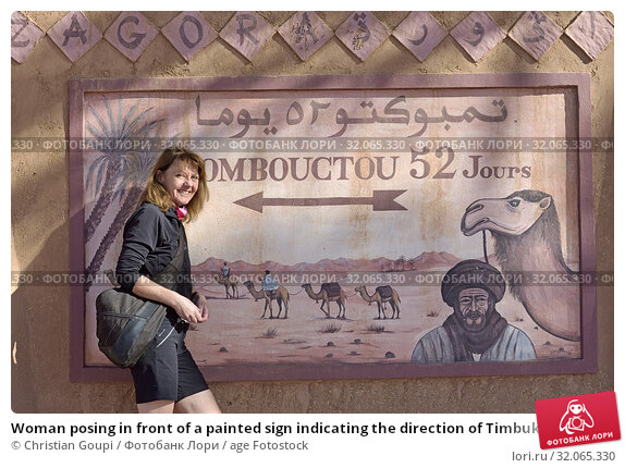 Woman posing in front of a painted sign indicating the direction of Timbuktu at 52 days of camel travel, Zagora, Draa River valley, Province of Zagora... (2019 год). Редакционное фото, фотограф Christian Goupi / age Fotostock / Фотобанк Лори