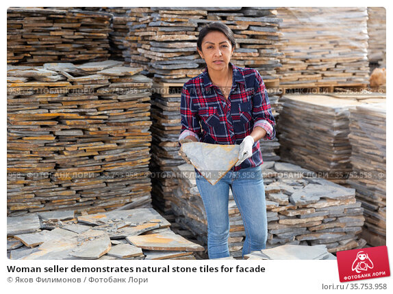 Woman seller demonstrates natural stone tiles for facade. Стоковое фото, фотограф Яков Филимонов / Фотобанк Лори