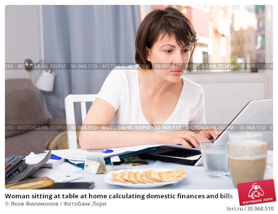 Купить «Woman sitting at table at home calculating domestic finances and bills», фото № 30968510, снято 23 июля 2019 г. (c) Яков Филимонов / Фотобанк Лори