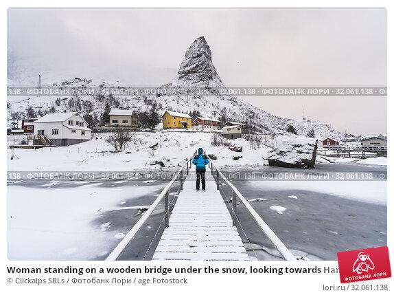 Woman standing on a wooden bridge under the snow, looking towards Hammarskaftet peak. Reine, Nordland county, Northern Norway, Norway. Стоковое фото, фотограф Clickalps SRLs / age Fotostock / Фотобанк Лори