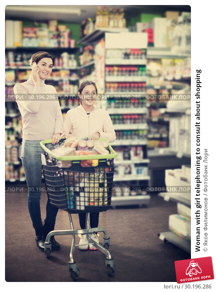 Купить «Woman with girl telephoning to consult about shopping», фото № 30196286, снято 5 января 2017 г. (c) Яков Филимонов / Фотобанк Лори