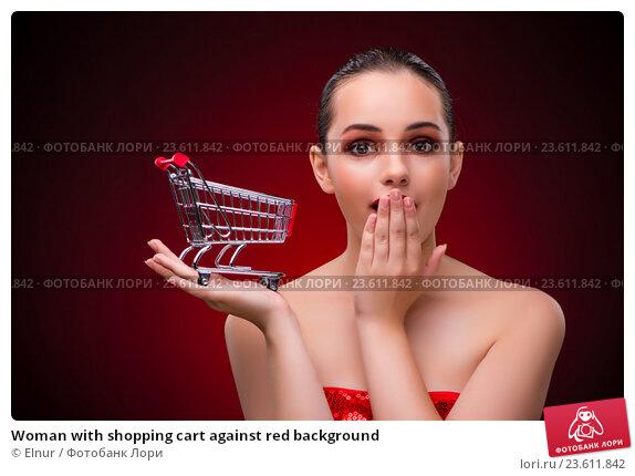 Купить «Woman with shopping cart against red background», фото № 23611842, снято 18 июля 2016 г. (c) Elnur / Фотобанк Лори