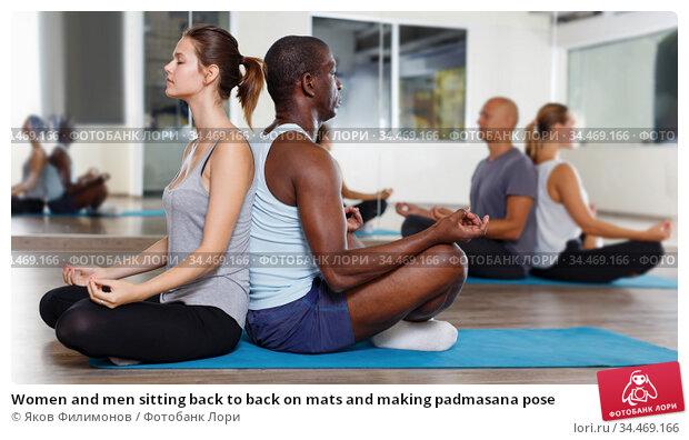 Women and men sitting back to back on mats and making padmasana pose. Стоковое фото, фотограф Яков Филимонов / Фотобанк Лори