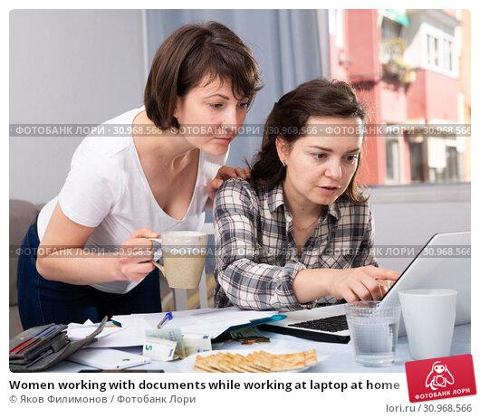 Купить «Women working with documents while working at laptop at home», фото № 30968566, снято 16 июля 2019 г. (c) Яков Филимонов / Фотобанк Лори