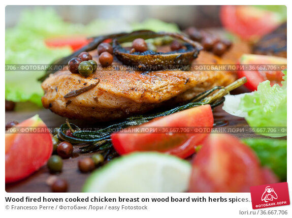 Wood fired hoven cooked chicken breast on wood board with herbs spices... Стоковое фото, фотограф Francesco Perre / easy Fotostock / Фотобанк Лори