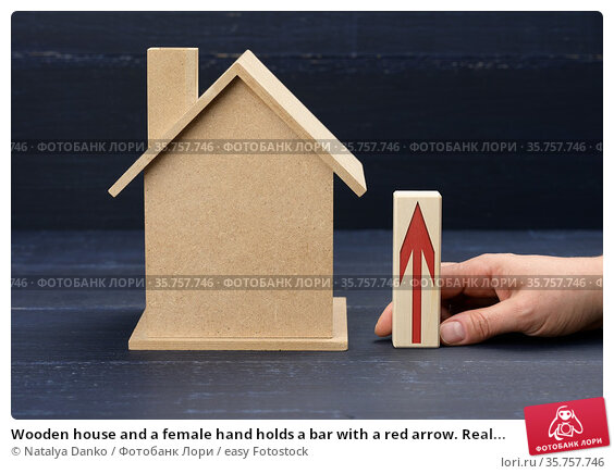 Wooden house and a female hand holds a bar with a red arrow. Real... Стоковое фото, фотограф Natalya Danko / easy Fotostock / Фотобанк Лори