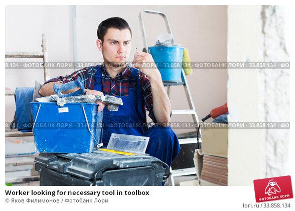 Купить «Worker looking for necessary tool in toolbox», фото № 33858134, снято 21 мая 2017 г. (c) Яков Филимонов / Фотобанк Лори