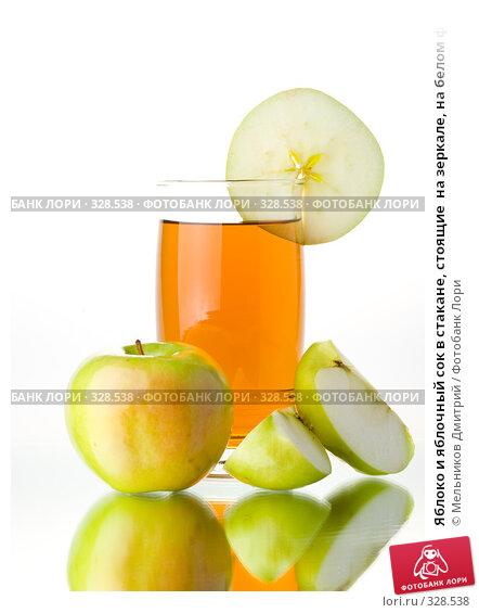 Купить «Яблоко и яблочный сок в стакане, стоящие  на зеркале, на белом фоне», фото № 328538, снято 14 июня 2008 г. (c) Мельников Дмитрий / Фотобанк Лори