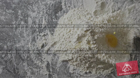 Купить «Yolk falls Into the flour on a kitchen table. Preparation homemade pastry. Slow motion, Full HD video, 240fps, 1080p. Top view», видеоролик № 33886910, снято 4 июля 2020 г. (c) Ярослав Данильченко / Фотобанк Лори