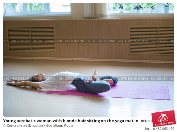 Young acrobatic woman with blonde hair sitting on the yoga mat in lotus pose and leaning back. Стоковое фото, фотограф Константин Шишкин / Фотобанк Лори