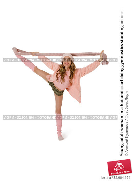 Young adult woman in a hat and scarf doing gymnastics standing on one leg. Стоковое фото, фотограф Алексей Кузнецов / Фотобанк Лори
