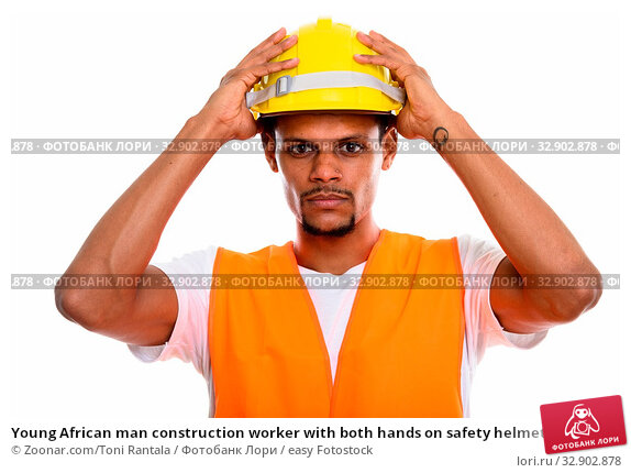 Young African man construction worker with both hands on safety helmet. Стоковое фото, фотограф Zoonar.com/Toni Rantala / easy Fotostock / Фотобанк Лори