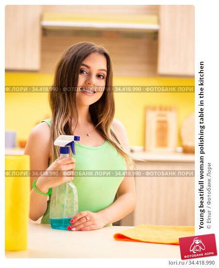 Young beatifull woman polishing table in the kitchen. Стоковое фото, фотограф Elnur / Фотобанк Лори