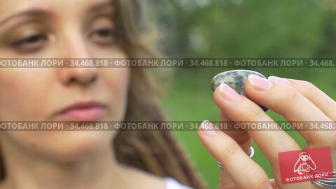Young beautiful girl with dreadlocks holds in hand azurite, natural stone outdoors during morning near her face with perfect skin. Стоковое видео, видеограф Ольга Балынская / Фотобанк Лори