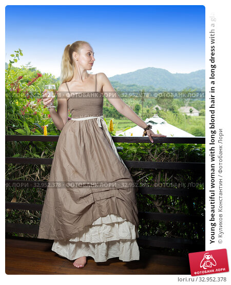 Young beautiful woman with long blond hair in a long dress with a glass of wine standing on the terrace and looking at the tropics. Стоковое фото, фотограф Куликов Константин / Фотобанк Лори