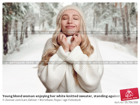 Young blond woman enjoying her white knitted sweater, standing against... Стоковое фото, фотограф Zoonar.com/Lars Zahner / age Fotostock / Фотобанк Лори
