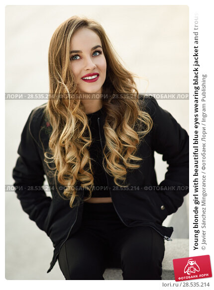 Купить «Young blonde girl with beautiful blue eyes wearing black jacket and trousers outdoors. Pretty russian female with long wavy hair hairstyle. Woman in urban background.», фото № 28535214, снято 24 января 2017 г. (c) Ingram Publishing / Фотобанк Лори