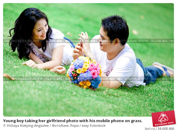 Young boy taking her girlfriend photo with his mobile phone on grass. Стоковое фото, фотограф Vichaya Kiatying-Angsulee / easy Fotostock / Фотобанк Лори