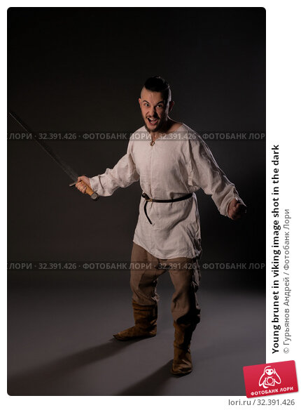 Купить «Young brunet in viking image shot in the dark», фото № 32391426, снято 12 октября 2019 г. (c) Гурьянов Андрей / Фотобанк Лори