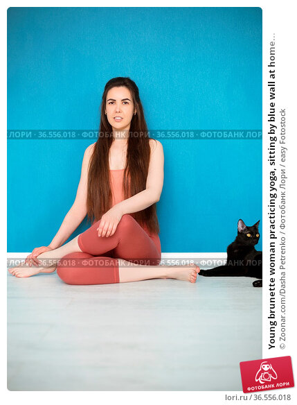 Young brunette woman practicing yoga, sitting by blue wall at home... Стоковое фото, фотограф Zoonar.com/Dasha Petrenko / easy Fotostock / Фотобанк Лори