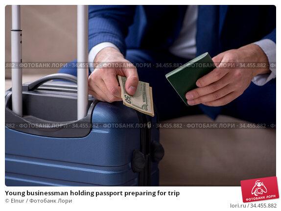 Young businessman holding passport preparing for trip. Стоковое фото, фотограф Elnur / Фотобанк Лори