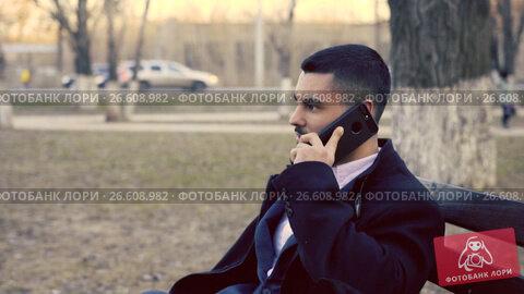Купить «Young Businessman or Employee Sitting Outdoors, Using Smartphone», видеоролик № 26608982, снято 25 апреля 2017 г. (c) Pavel Biryukov / Фотобанк Лори