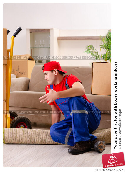Young contractor with boxes working indoors. Стоковое фото, фотограф Elnur / Фотобанк Лори