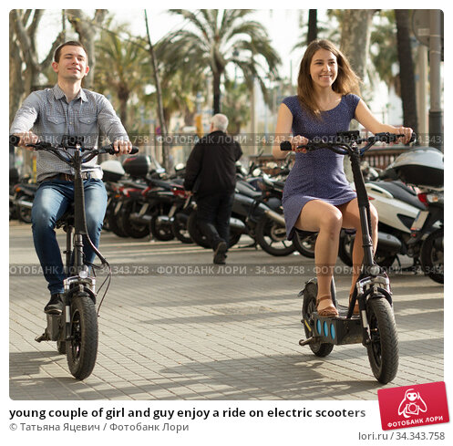 young couple of girl and guy enjoy a ride on electric scooters. Стоковое фото, фотограф Татьяна Яцевич / Фотобанк Лори