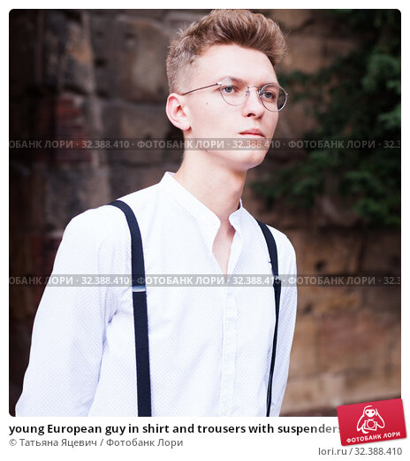 Купить «young European guy in shirt and trousers with suspenders walking around city», фото № 32388410, снято 27 июня 2018 г. (c) Татьяна Яцевич / Фотобанк Лори