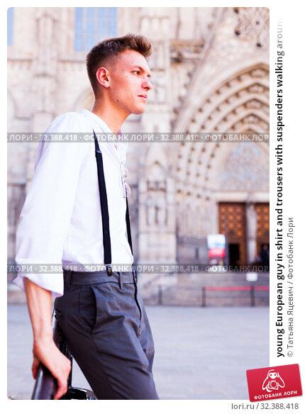 Купить «young European guy in shirt and trousers with suspenders walking around city», фото № 32388418, снято 27 июня 2018 г. (c) Татьяна Яцевич / Фотобанк Лори