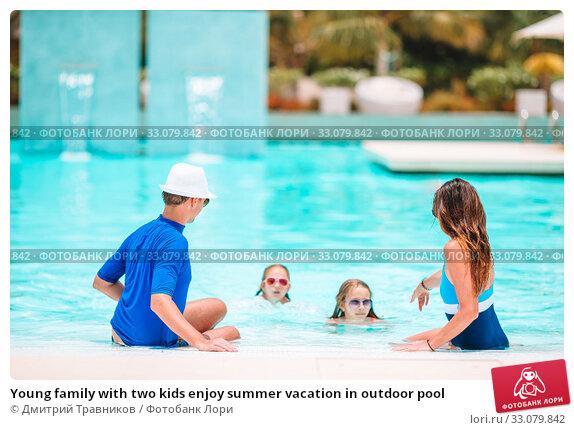 Купить «Young family with two kids enjoy summer vacation in outdoor pool», фото № 33079842, снято 19 февраля 2016 г. (c) Дмитрий Травников / Фотобанк Лори