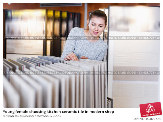 Young female choosing kitchen ceramic tile in modern shop. Стоковое фото, фотограф Яков Филимонов / Фотобанк Лори