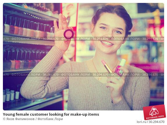Купить «Young female customer looking for make-up items», фото № 30294670, снято 21 февраля 2017 г. (c) Яков Филимонов / Фотобанк Лори