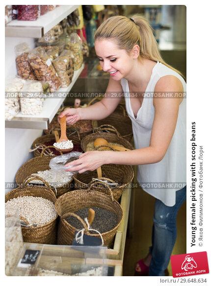 Купить «Young female picking with scoop beans», фото № 29648634, снято 23 марта 2019 г. (c) Яков Филимонов / Фотобанк Лори