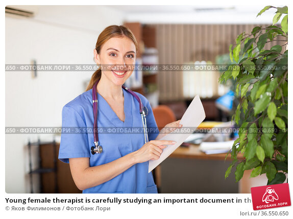 Young female therapist is carefully studying an important document in the office. Стоковое фото, фотограф Яков Филимонов / Фотобанк Лори