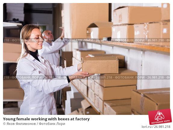 Купить «Young female working with boxes at factory», фото № 26981218, снято 22 апреля 2017 г. (c) Яков Филимонов / Фотобанк Лори