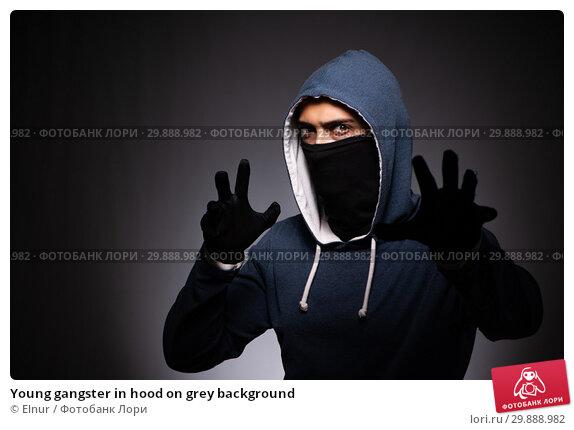 Купить «Young gangster in hood on grey background», фото № 29888982, снято 27 сентября 2018 г. (c) Elnur / Фотобанк Лори