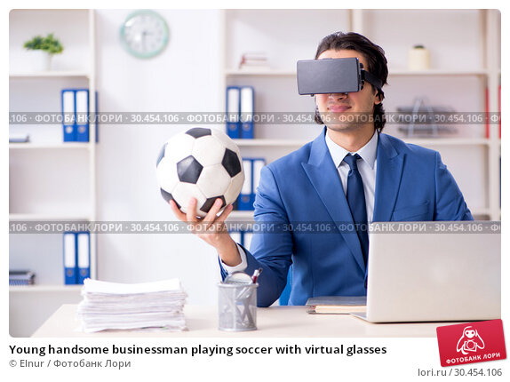 Young handsome businessman playing soccer with virtual glasses. Стоковое фото, фотограф Elnur / Фотобанк Лори