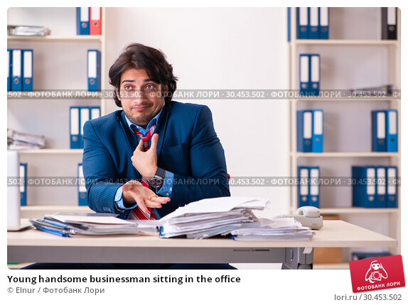 Young handsome businessman sitting in the office. Стоковое фото, фотограф Elnur / Фотобанк Лори