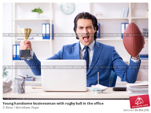 Young handsome businessman with rugby ball in the office. Стоковое фото, фотограф Elnur / Фотобанк Лори