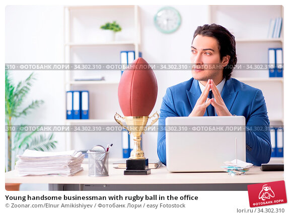 Young handsome businessman with rugby ball in the office. Стоковое фото, фотограф Zoonar.com/Elnur Amikishiyev / easy Fotostock / Фотобанк Лори