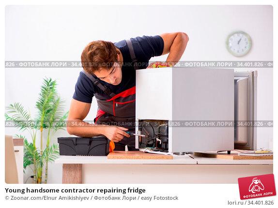 Young handsome contractor repairing fridge. Стоковое фото, фотограф Zoonar.com/Elnur Amikishiyev / easy Fotostock / Фотобанк Лори