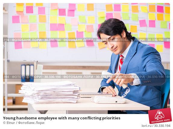 Купить «Young handsome employee with many conflicting priorities», фото № 30330194, снято 16 октября 2018 г. (c) Elnur / Фотобанк Лори