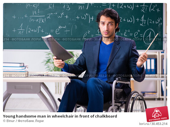 Young handsome man in wheelchair in front of chalkboard. Стоковое фото, фотограф Elnur / Фотобанк Лори