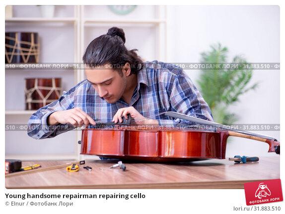 Купить «Young handsome repairman repairing cello», фото № 31883510, снято 4 апреля 2019 г. (c) Elnur / Фотобанк Лори