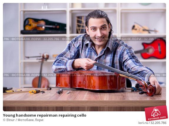 Купить «Young handsome repairman repairing cello», фото № 32205786, снято 4 апреля 2019 г. (c) Elnur / Фотобанк Лори