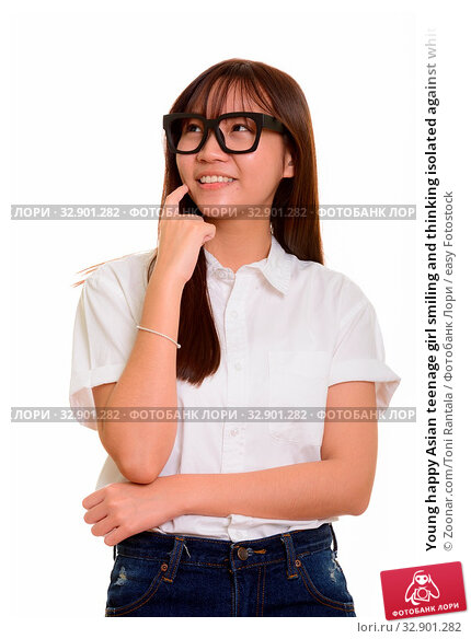 Young happy Asian teenage girl smiling and thinking isolated against white background. Стоковое фото, фотограф Zoonar.com/Toni Rantala / easy Fotostock / Фотобанк Лори