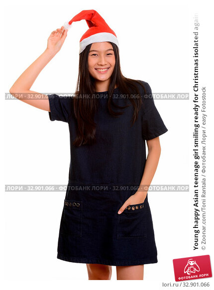 Young happy Asian teenage girl smiling ready for Christmas isolated against white background. Стоковое фото, фотограф Zoonar.com/Toni Rantala / easy Fotostock / Фотобанк Лори